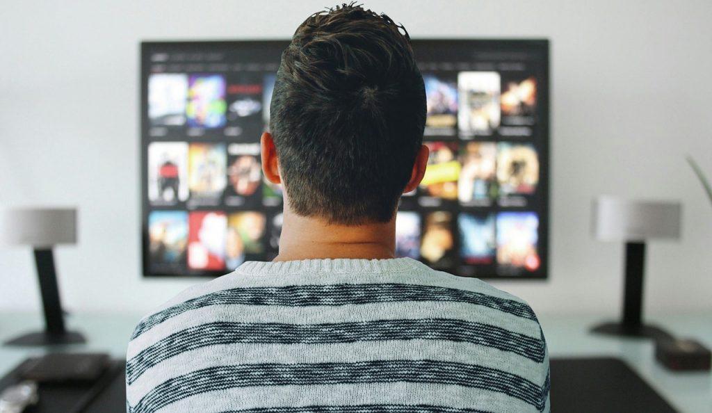 בן אדם צופה בנטפליקס בטלוויזיה